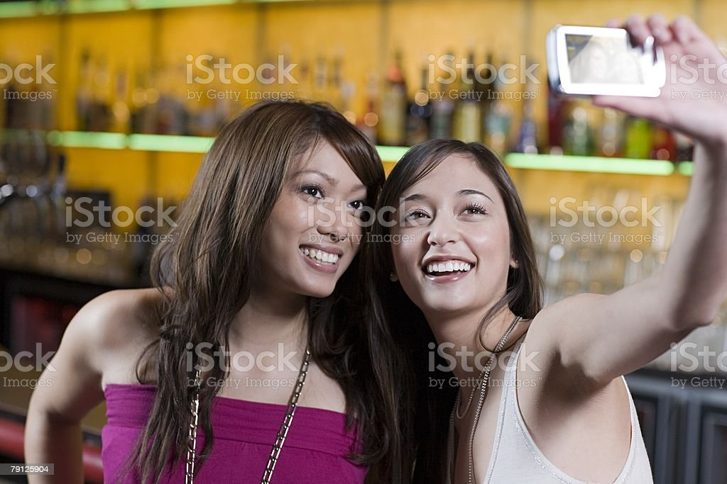 Young women taking picture in a bar royalty-free 스톡 사진