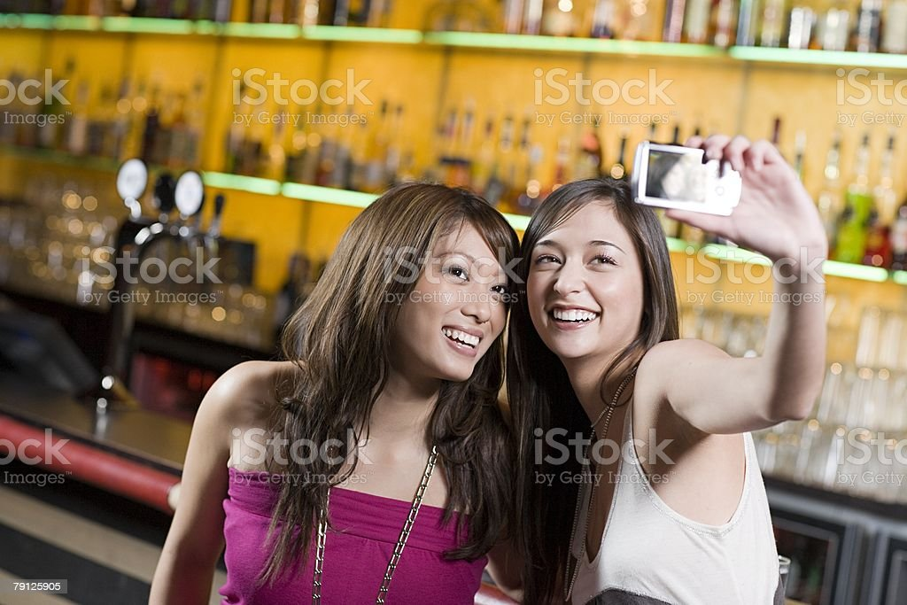 Young women taking picture in a bar 免版稅 stock photo