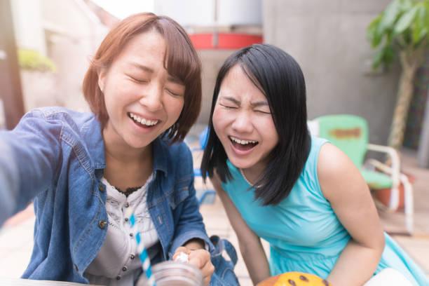 完全にこぼれるような笑顔で selfie 写真を撮る若い女性 ストックフォト