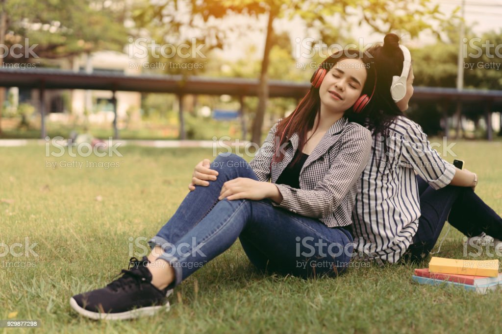 Young women teenagers together students listening music with headphone university college outdoor with school folder and relaxing having fun enjoy or study online concept stock photo