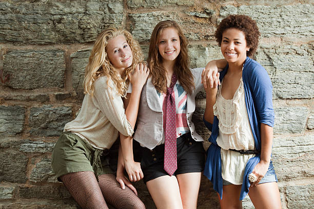 Young Women: Three Happy Smiling Teenage Girls by Stone Wall stock photo