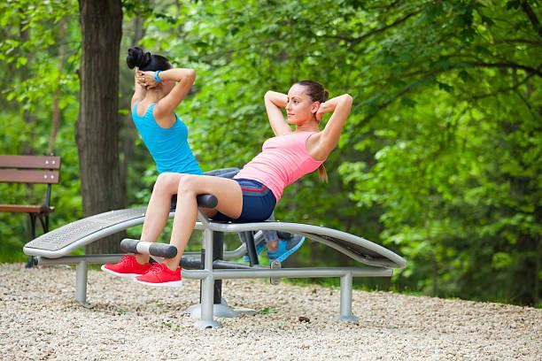 Junge Frauen Ausbildung auf sit-up-Bank im park – Foto