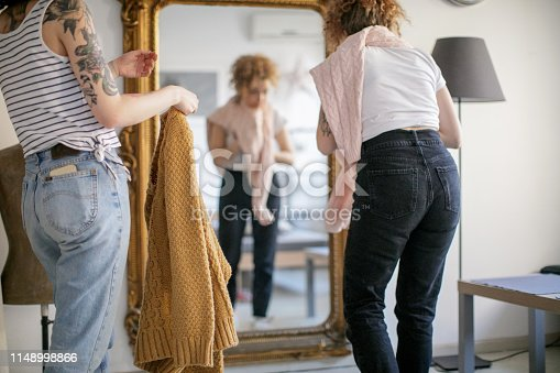 Young woman helping her friend trying on a sweater in front of the mirror
