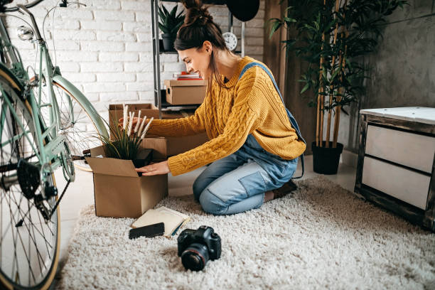 Young women unpacking in new rented apartment stock photo