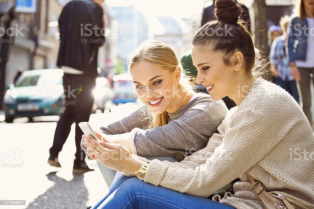 Young women using smart phone Two young women sitting on the city street and using a smart phone. 20-24 Years Stock Photo