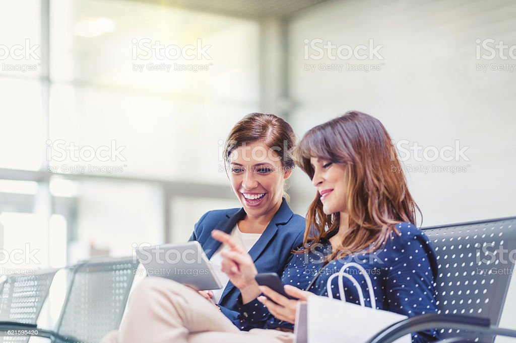 Young women waiting at airport lounge stock photo