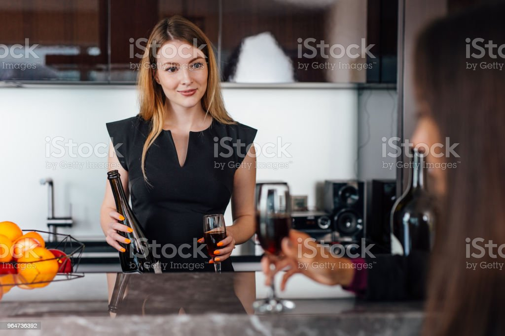 Young women wearing elegant black dress holding a bottle of red wine and a glass standing at kitchen bar looking at her female friend royalty-free stock photo