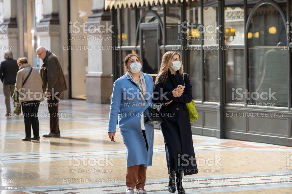 Mujeres jóvenes con máscara facial blanca caminando por la Galleria Vittorio Emanuele II. - Foto de stock de Adulto libre de derechos