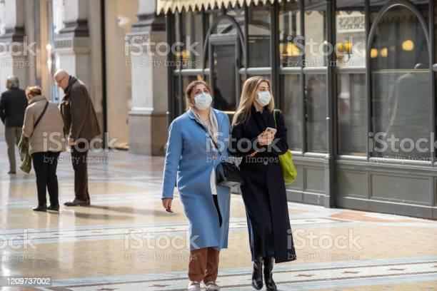 Mujeres Jóvenes Con Máscara Facial Blanca Caminando Por La Galleria Vittorio Emanuele Ii Foto de stock y más banco de imágenes de Adulto