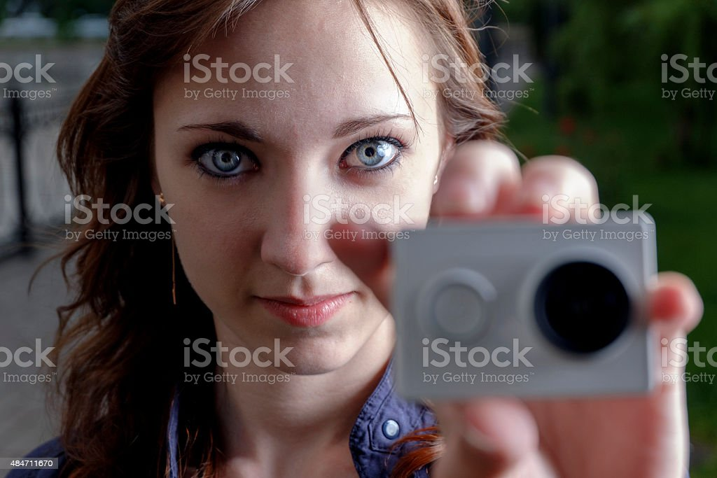 Young women with action camera in hand closeup. Peoples journalism stock photo