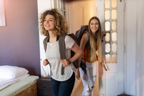 Young women with backpacks arriving to a youth hostel stock photo