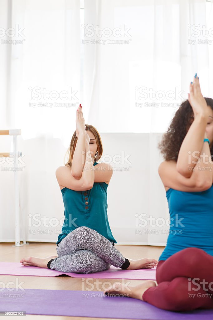 Young women with closed eyes sitting on mat and meditate royalty-free stock photo