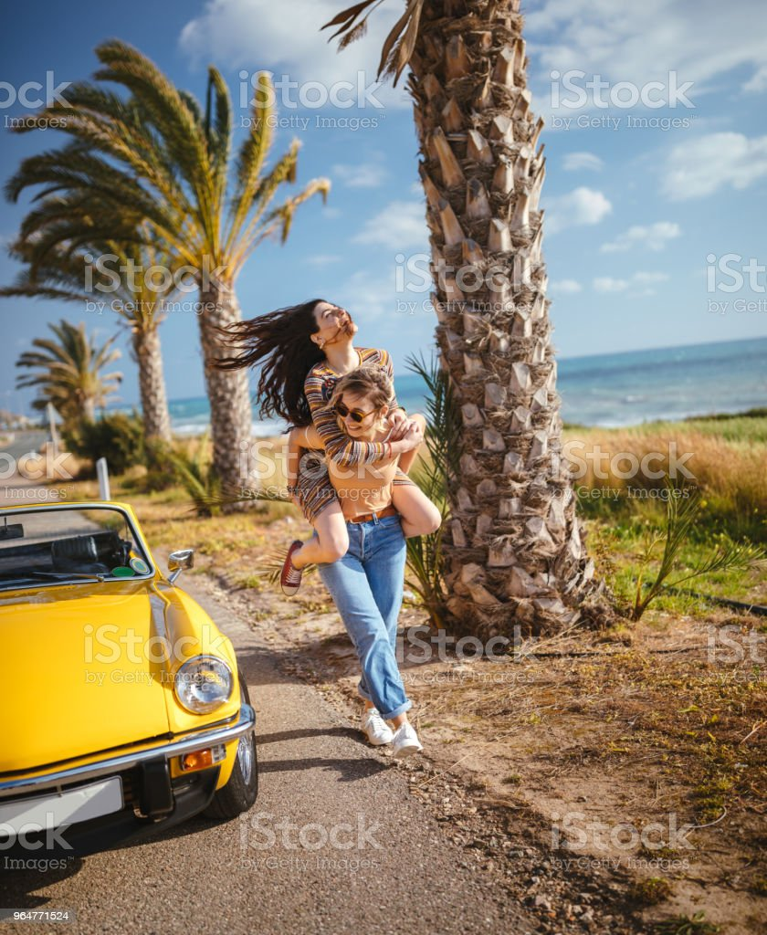 Young women with convertible car having fun with piggyback ride royalty-free stock photo