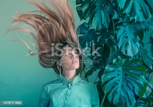 Young women with flying hair and monstera