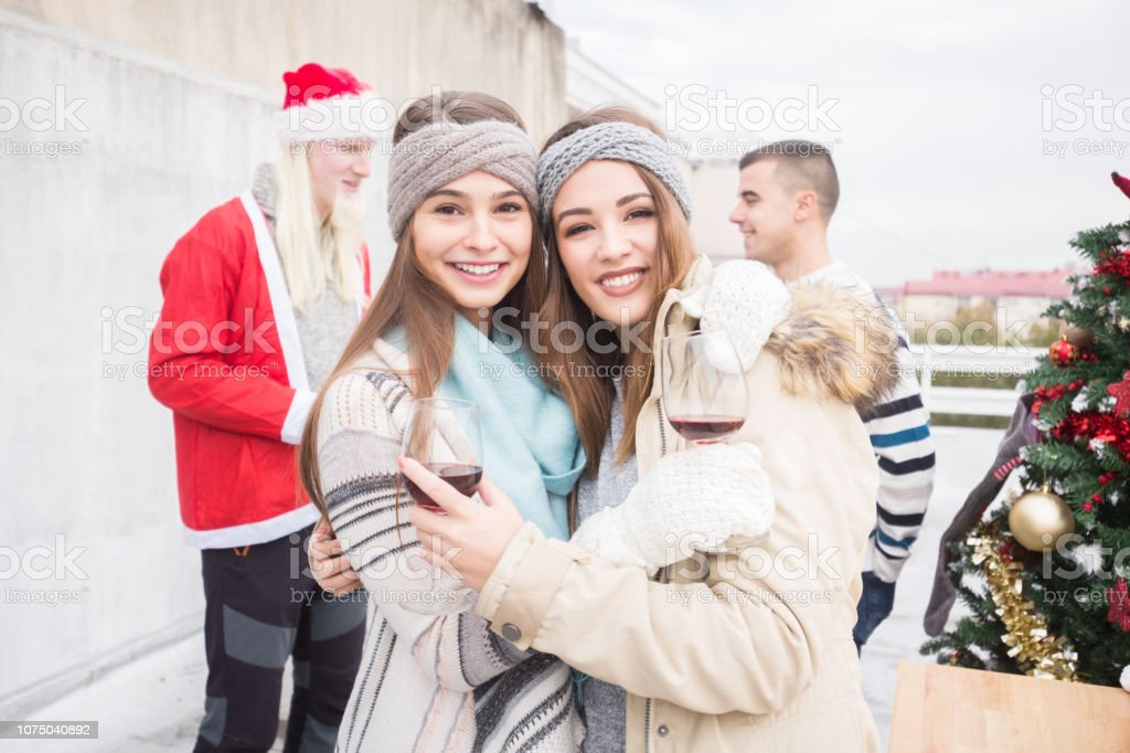 Young women with friends on balcony celebrating Christmas stock photo