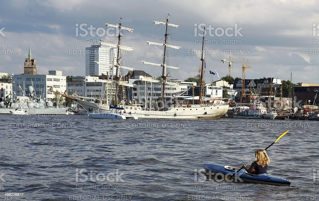 Young women with kayak in front of a sailing ship stock photo