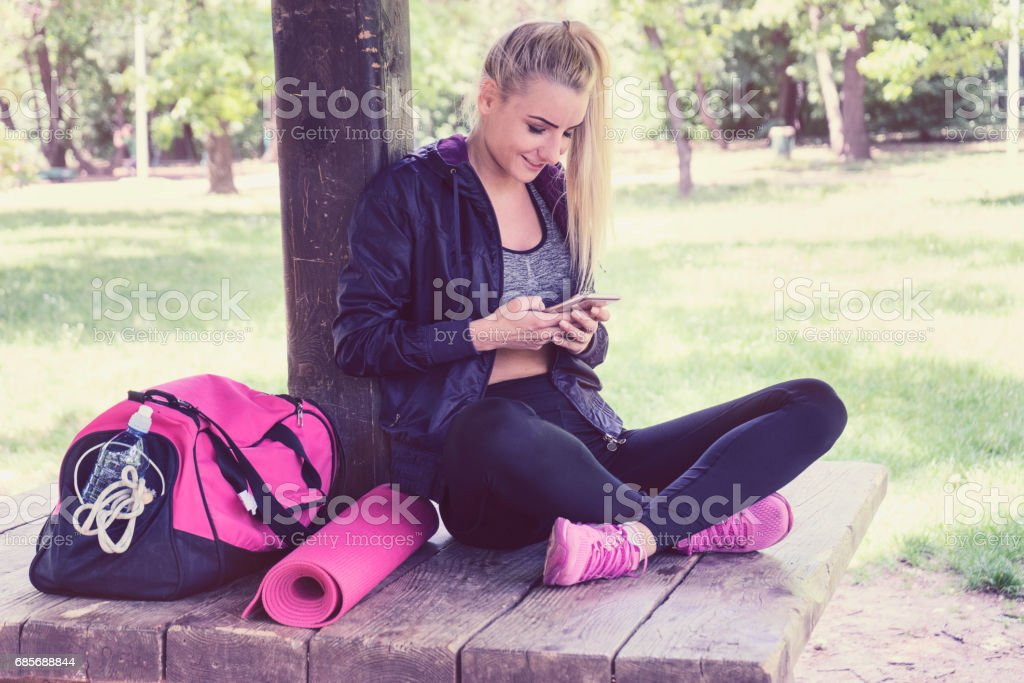 Young women with phone resting after training. foto de stock royalty-free