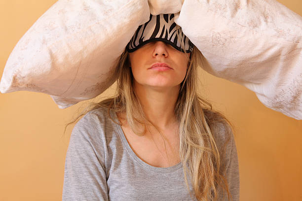 Young women with pillow Sleepy young women with pillow and sleeping eye mask still on. aftereffect stock pictures, royalty-free photos & images