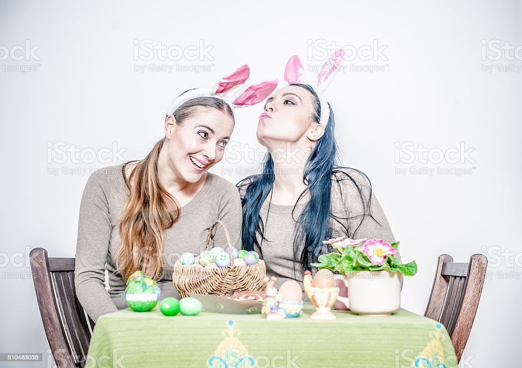 Young women with rabbit ears having fun with easter eggs stock photo