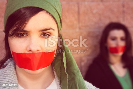 Young woman with serious expression is looking at the camera. She is wearing a piece of red tape over her mouth as a sign of silent protest. Activist is wearing a green head scarf. A second young woman is also wearing tape over her mouth in the background, while leaning against a stone wall.