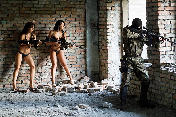 Young women with rifles and soldier stock photo