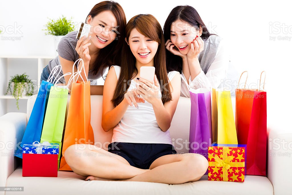 young women with shopping bags and looking at smart phone stock photo
