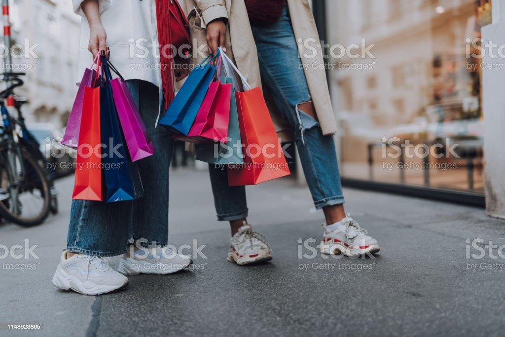 Jonge vrouwen met boodschappentassen staan op straat - Royalty-free Alleen volwassenen Stockfoto