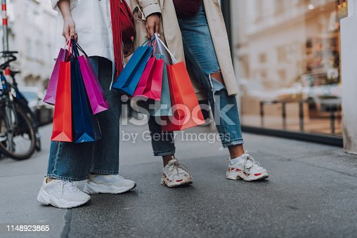 Look what we bought. Close up of two girl in jeans and sneakers holding colorful shopping bags
