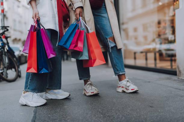 junge frauen mit einkaufstaschen stehen auf der straße - konsum stock-fotos und bilder