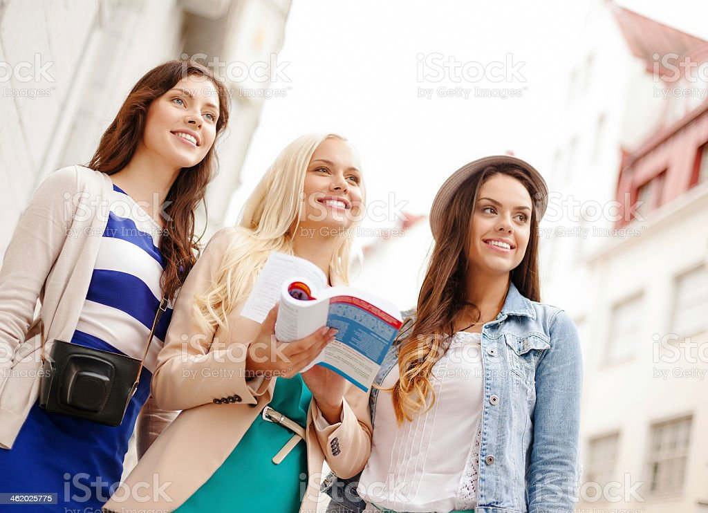 Young women with tourist book and camera in city stock photo
