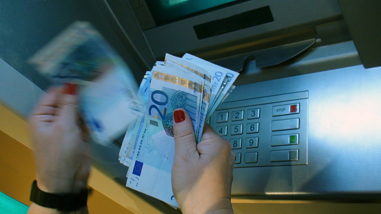 istock Young Women Withdrawing And Counting European Currency Note From ATM 478677872