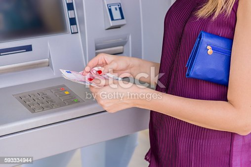 istock Young Women Withdrawing And Counting European Currency 593334944
