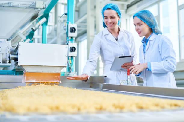 junge frauen arbeiten bei food factory - grundnahrungsmittel stock-fotos und bilder