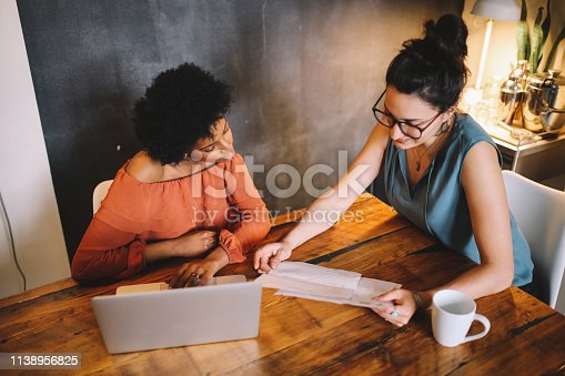 Young mixed race women working in downtown Los Angeles co-working space, going through the paperwork in a small startup company.