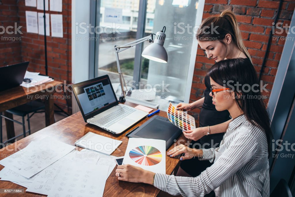Young women working on a new web design using color swatches and sketches sitting at desk in modern office stock photo