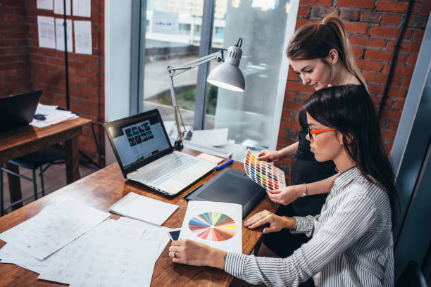 young women working on a new web design using color swatches and sketches sitting at desk in modern office - logo design stock photos and pictures