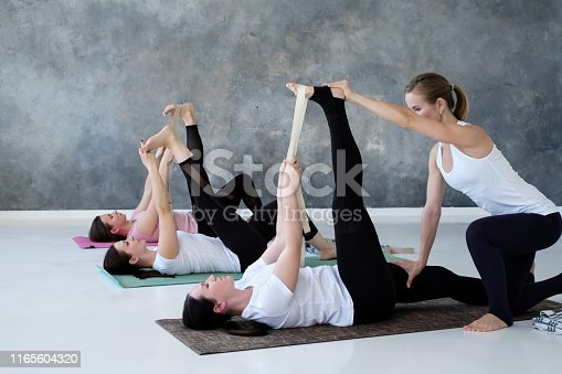 Group of young women working out in yoga studio, doing exercise on floor, lying in Supta Padangushthasana, reclined variation of Extended Hand to Big Toe pose.