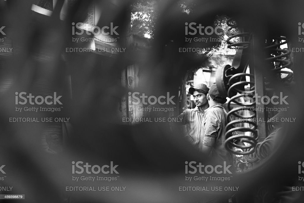 Young worker behind Shock Absorber, Karachi Scrapyard royalty-free stock photo