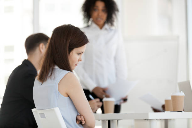 Young worker feels offended frustrated during meeting at work Diverse businesspeople in office during briefing focus on female worker feels guilty unhappy offended and frustrated having problem or disrespect from colleagues or made mistake, listens boss scolding cruel stock pictures, royalty-free photos & images