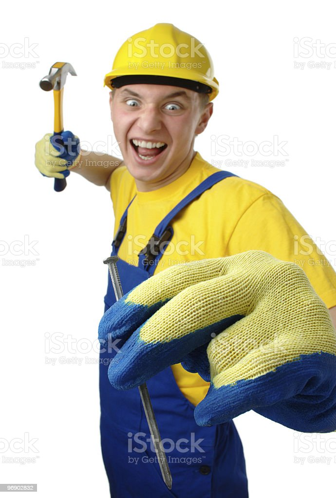 Young worker furiously hammering a nail royalty-free stock photo