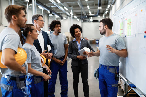 Young worker giving presentation in front of whiteboard in a factory. Young factory worker holding presentation about production development to company managers and his coworkers. manufacturing stock pictures, royalty-free photos & images