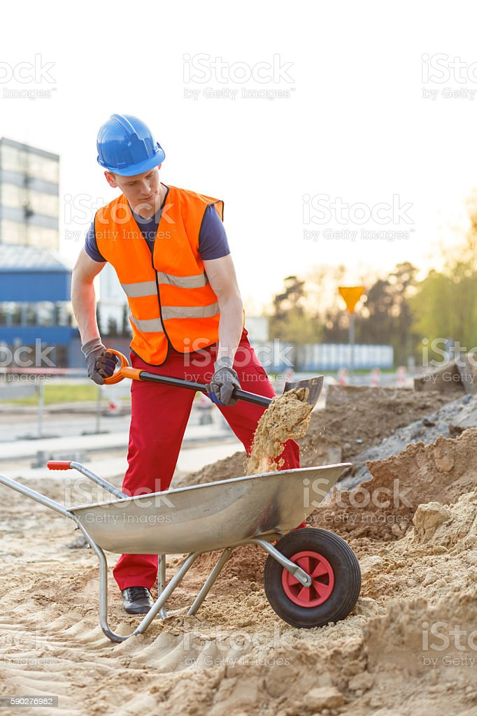 Young worker loading a wheelbarrow stock photo