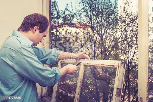 966792200 istock photo Young worker man restoring and fixing old wooden windows using a pair of pliers. Repairing interior of an old house or flat. Close-up of home DIY 1224778830