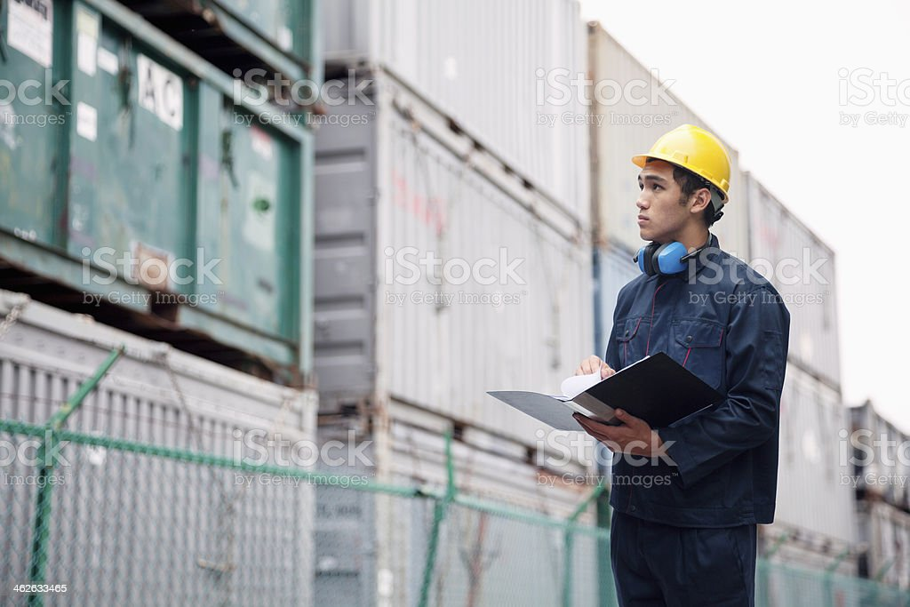 Young worker wearing protective workwear examining cargo in shipping yard royalty-free stock photo