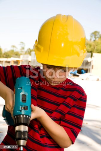 istock Young worker with cordless drill wearing hardhat at jobsite 93987920