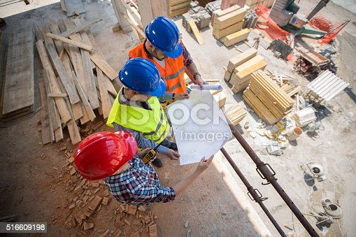 516607254istockphoto Young workers checking blue print at building place 516609198