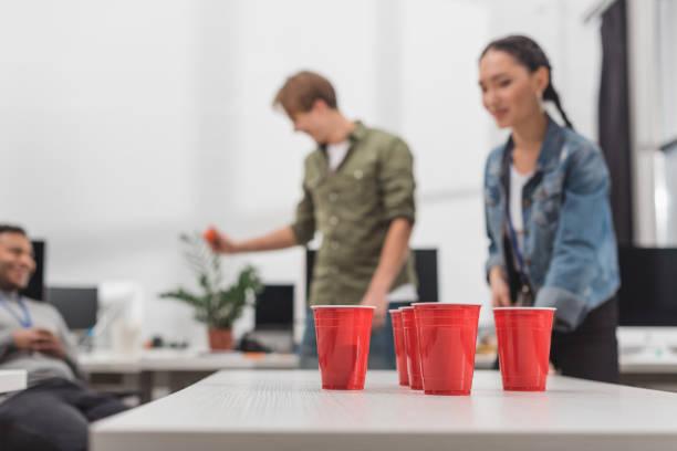 junge arbeitnehmer, bier pong im modernen büro feierabend spielen - lustige trinkspiele stock-fotos und bilder