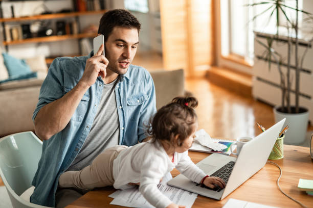 Young working father with small daughter talking on mobile phone at home. stock photo