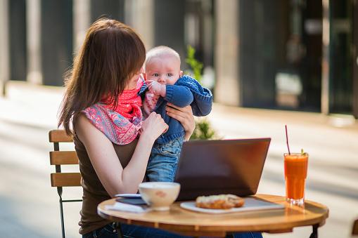 Trabajo Joven Madre Con Su Hijo En Una Cafetería Little Foto de stock y más banco de imágenes de Adulto