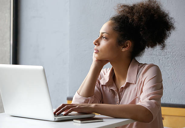 Young working woman looking out window Close up portrait of a young african american woman looking out window when working on laptop day dreaming stock pictures, royalty-free photos & images